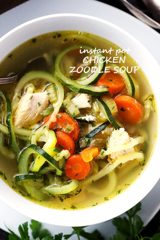 White bowl containing chicken zoodle soup with zucchini noodles, carrots and chicken.