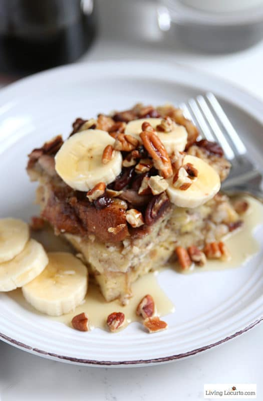 A white plate with french toast, sliced bananas topped with pecans, silver fork.