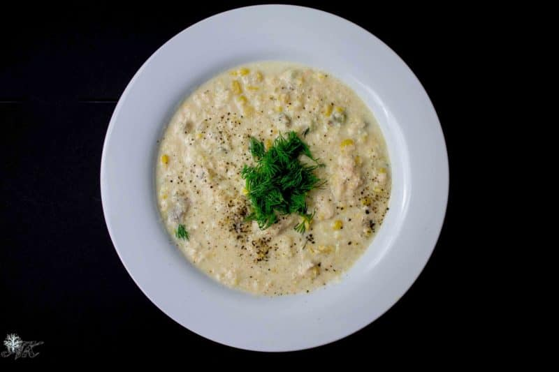 White bowl containing Salmon Chowder with corn, topped with fresh dill.