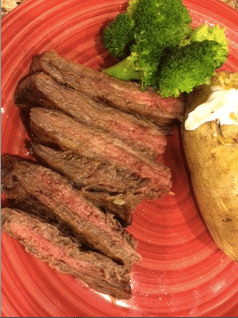 A red plate with cut flank steak, broccoli and a baked potato.
