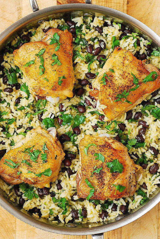 Silver pan containing black beans, rice and chicken thighs, topped with parsley.