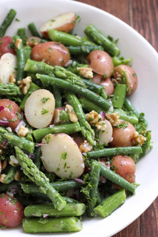 A white bowl containing new potatoes, asparagus and green beans, topped with herbs.