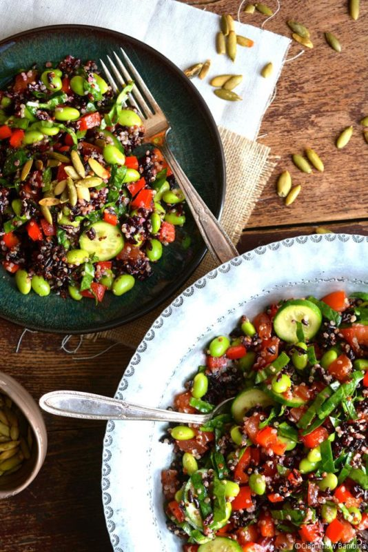 A salad plate of quinoa with Edamame & Black Rice sitting on a wooden table with a silver fork, large bowl of salad with serving spoon.