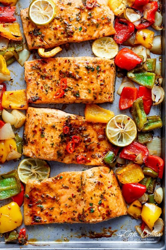 A silver sheet pan with 4 filets of salmon with sliced roasted onion, yellow, green and red peppers and grilled lemon slices.