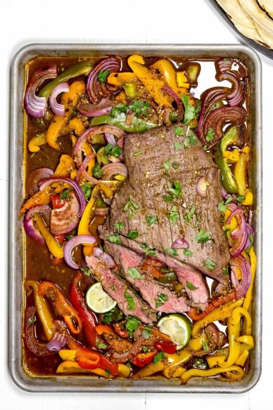 Sheet pan containing flank steak, red onions, green, red and yellow peppers.