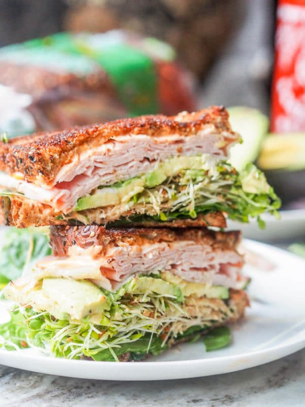 A double decker turkey, avocado and bean sprout salad sitting on a white plate.