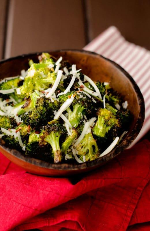 Garlic Roasted Broccoli in a wooden bowl topped with parmesan sitting on a table with a red napkin.