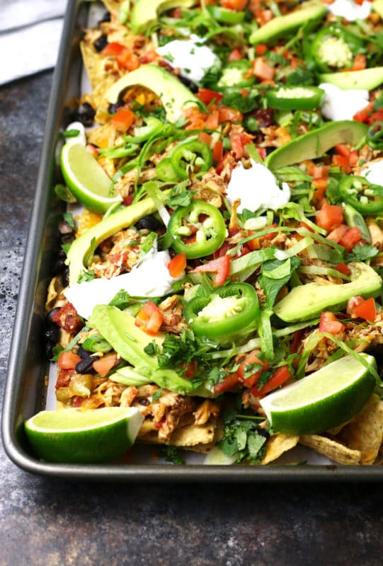 Sheet pan with tortilla chips topped with cooked chicken, cheese, tomatoes, jalapenos, black beans, lemon wedges and sour cream.