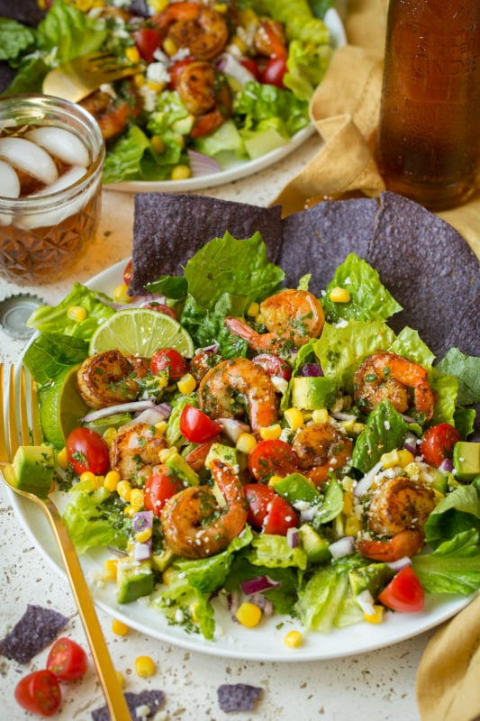 A white plate with blue corn chips, shrimp, avocado, tomatoes and corn on a white table with gold fork.