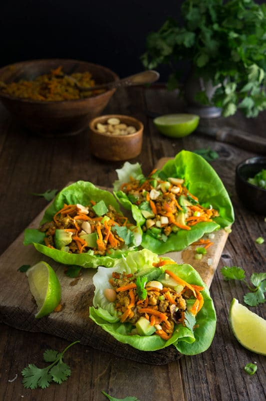 3 leaves of bibb lettuce, each containing chicken, carrots, avocado and peanuts on wood table with 2 lime slices and sprigs of cilantro.