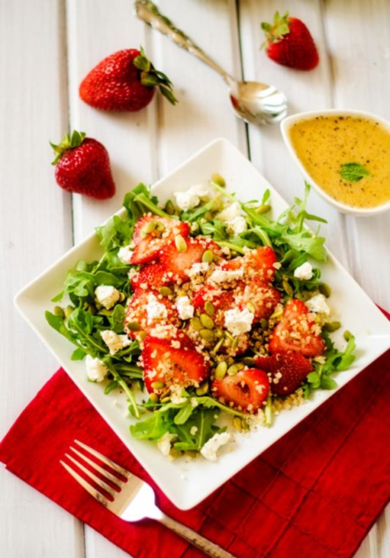 White plate with arugula lettuce topped with quinoa, strawberries and feta cheese sitting on a table with a fork, a red napkin and bowl of vinaigrette dressing.