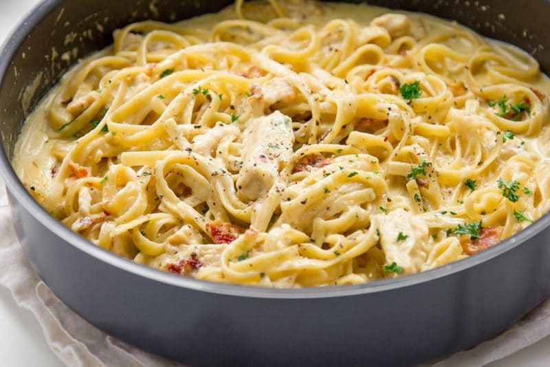 Black pan containing chicken alfredo topped with bacon and parsley, sitting on a white napkin.