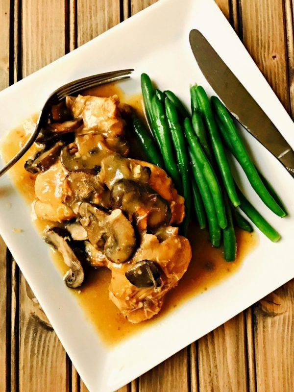 White plate sitting on a wooden table containing chicken marsala topped with mushrooms and green beans, a fork and knife.
