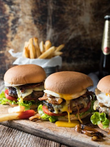 Wooden slab containing 3 cheeseburgers with melted cheese, tomatoes and lettuce, french fries in the background.