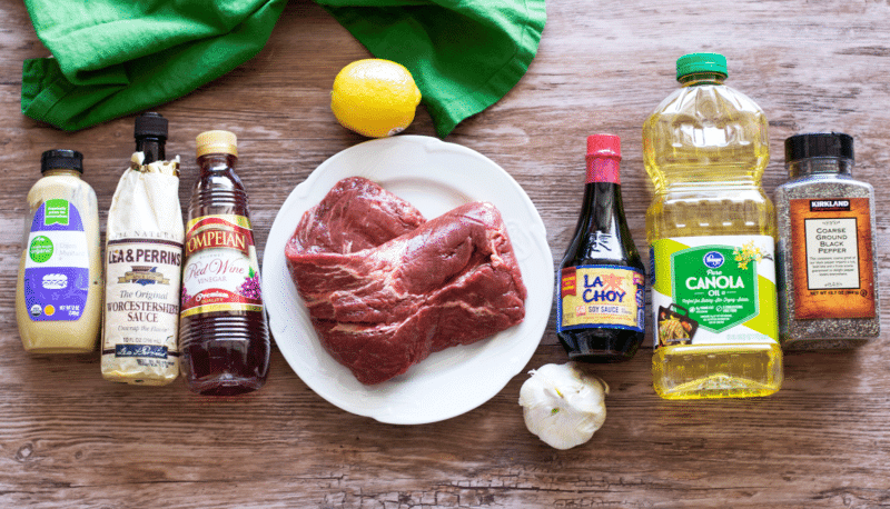 Table containing ingredients to make flank steak including Dijon mustard, worcestershire sauce, red wine vinegar, lemon, garlic, soy sauce, canola oil and pepper.
