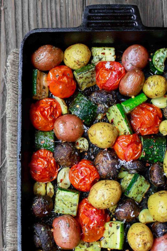 Roasted new potatoes, tomatoes, zucchini and asparagus in a black roasting pan sitting on a wooden table.