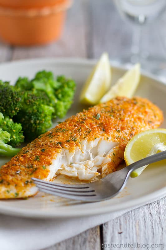 Parmesan crusted tilapia sitting on a white plate with a side of broccoli, lemon and fork on a white wood table.