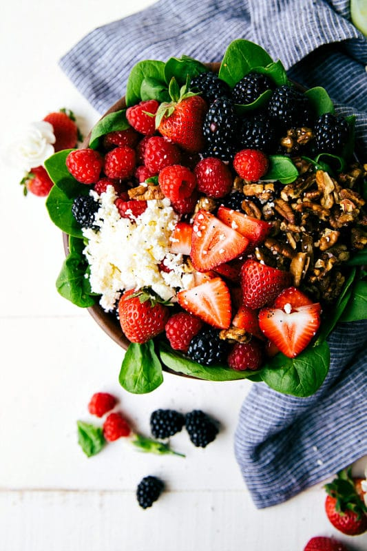 Spinach salad in a bowl containing raspberries, blackberries, strawberries, feta cheese and pecans, sitting on a white table with a blue napkin.