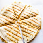 8 slices of chicken quesadilla sitting on a white table.