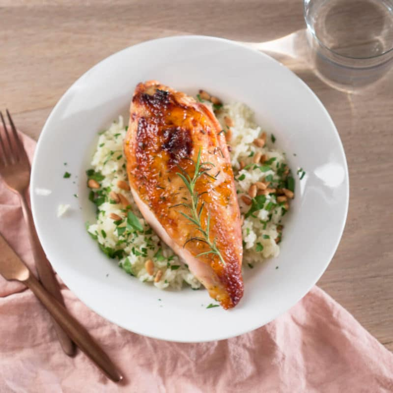 White plate containing rice and topped with apricot glazed chicken sitting on a brown table, criss crossed fork and knife.