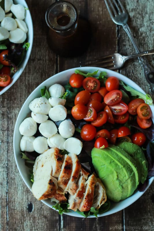 White bowl featuring Chicken Caprese salad topped with mozzarella cheese, halved cherry tomatoes and sliced avocado, sitting on a brown table, 2 crossed forks.