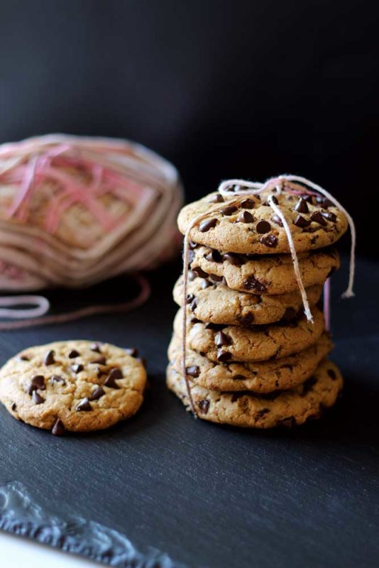 6 chocolate chip cookies tied with pink yarn sitting on a black slate, 1 cookie beside package of cookies.