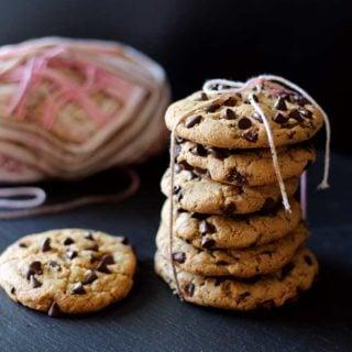 6 chocolate chip cookies tied with pink yarn sitting on a black slate, 1 cookie beside package of cookies.