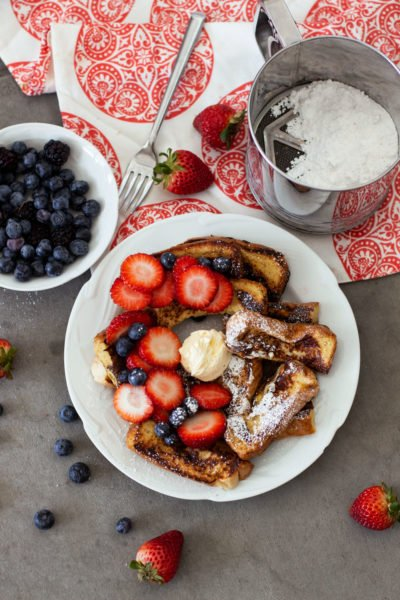 6 slices of french toast sitting on a white plate topped with maple syrup, side of fresh strawberries, grapes and blackberries.