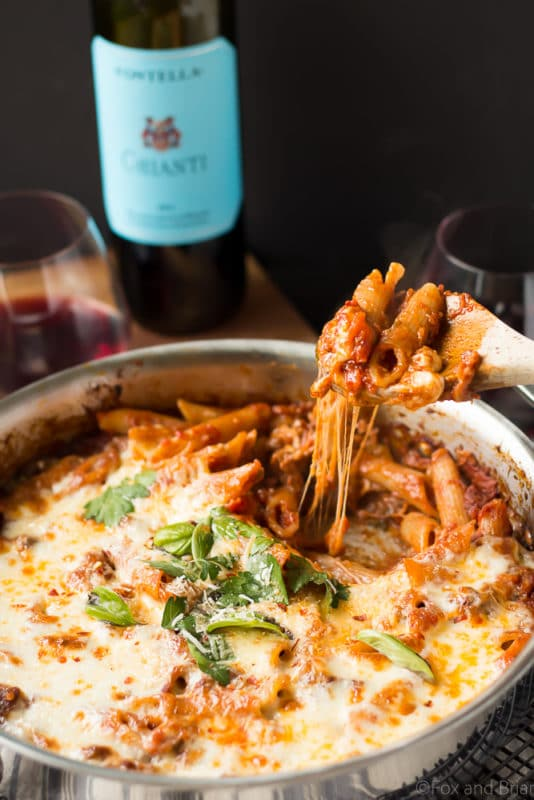One pot pasta bake with sausage and penne pasta in a cheesy marinara sauce, red wine in background.