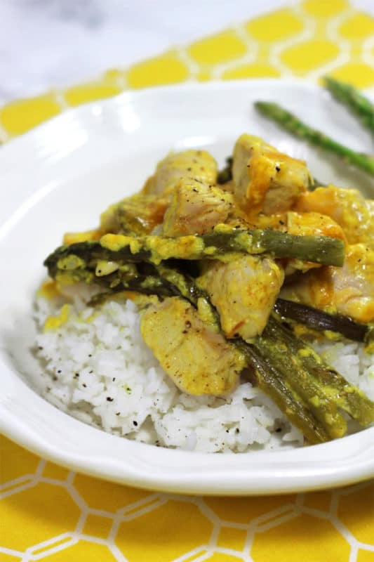White bowl containing curried chicken with a cream of chicken and cheese sauce served over asparagus and rice.