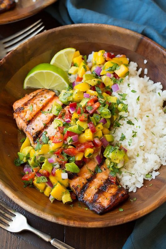 Brown bowl containing grilled salmon topped with mango salsa sitting on a bed of white rice, blue napkin and fork on table.