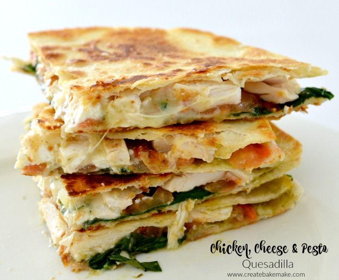 A stack of 4 chicken, cheese and pesto quesadillas sitting on a white table.