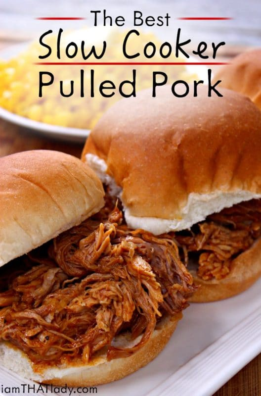 White plate featuring 2 BBQ pulled pork sandwiches sitting on a white plate, bowl of corn as a side.