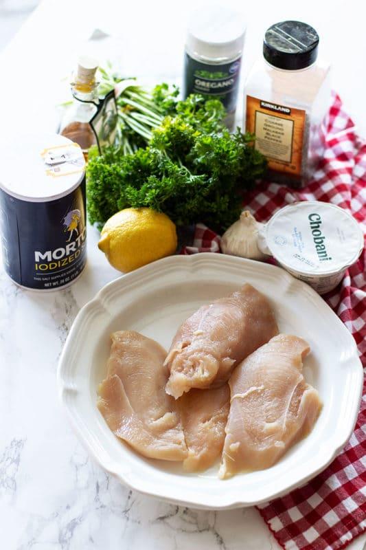 White marble table containing ingredients for making Greek Marinaded Chicken, garlic, greek yogurt, lemon juice, lemon zest, salt, parsley, oregano, garlic, olive and salt.