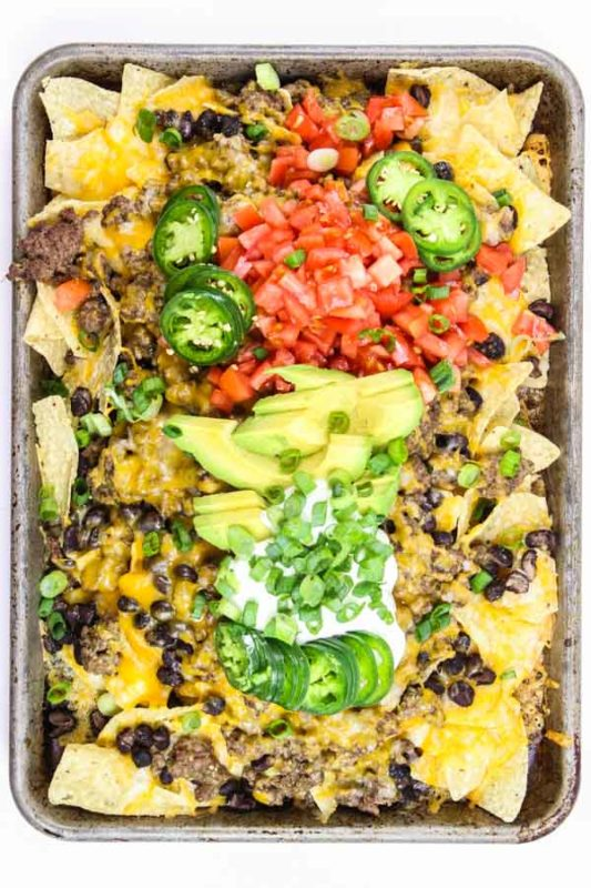 Sheet pan filled with nachos topped with beef, beans, cheese, tomatoes, jalapeno, sour cream and scallions.