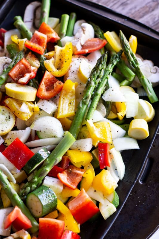 A pan seasoned with extra virgin olive oils, salt and pepper for fresh vegetables of asparagus, peppers, onions, squash and zucchini