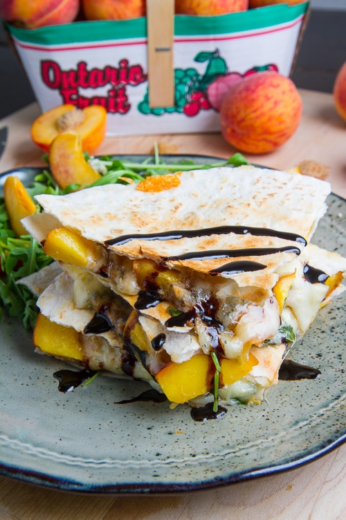 3 Peach Chicken and Gorgonzola Balsamic Quesadillas sitting on a blue plate, peaches sitting on a brown table.