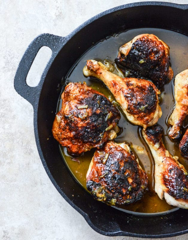 Cast Iron Skillet containing 6 beer citrus glazed chicken thighs and drumsticks sitting on a white table.