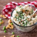 Glass bowl containing a pea, cauliflower and cashew salad sitting on a brown table, red and white gingham napkin with scattered peas and cashew nuts.
