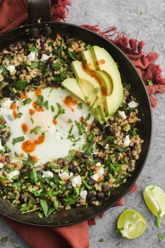 Cast Iron Skillet containing rice, bean, egg, avocado and cilantro, sitting on a red napkin on a gray table.