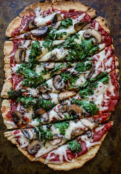 Gluten Free pizza topped with spinach, mushrooms, marinara sauce and mozzarella cheese sitting on a brown marble countertop.