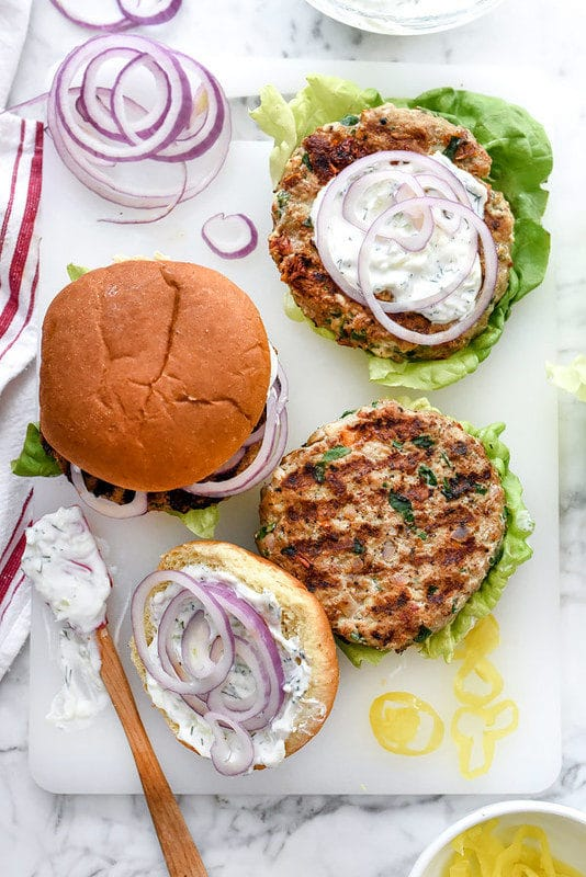White board containing 2 Greek Turkey burgers topped with red onions, lettuce and dill mayo sauce.