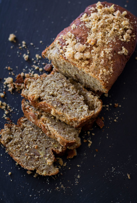 Sliced Banana Bread Loaf with Streusel-Nut Topping sitting on a black cutting board.