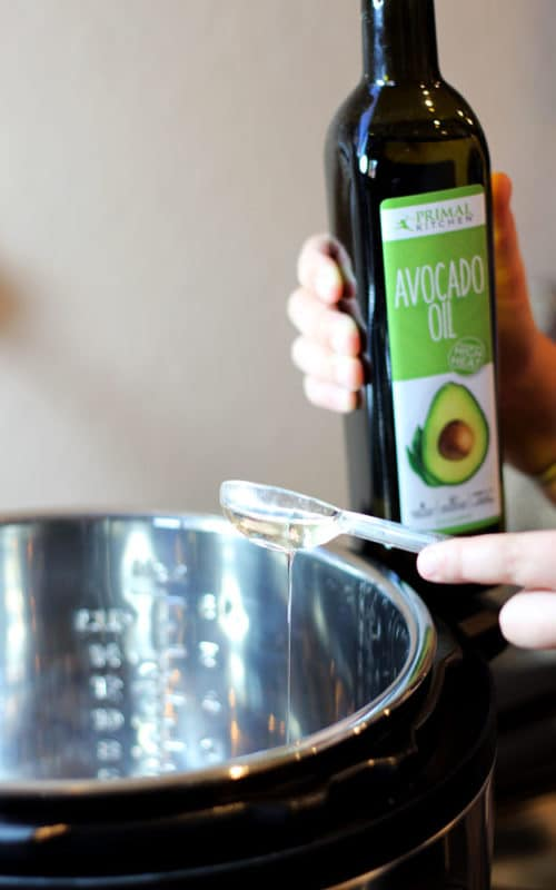 Tablespoon containing avocado oil being poured into Instant Pot.