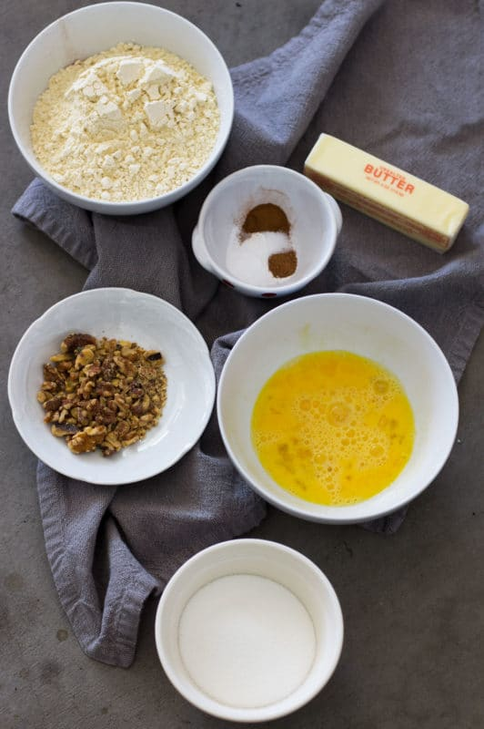 Ingredients to make banana bread, bowl of flour, eggs, butter, cinnamon, nutmeg, walnuts and sugar.