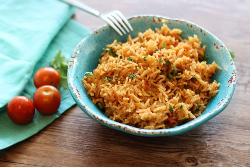 Instant pot mexican rice recipes worth repeating turquoise bowl containing mexican rice with serving fork on side of bowl heirloom tomatoes and forumfinder Image collections