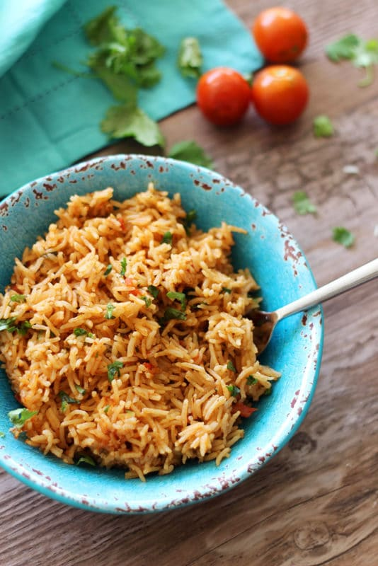 Instant pot mexican rice recipes worth repeating turquoise bowl sitting on a brown table containing mexican rice heirloom tomatoes and cilantro on forumfinder Image collections