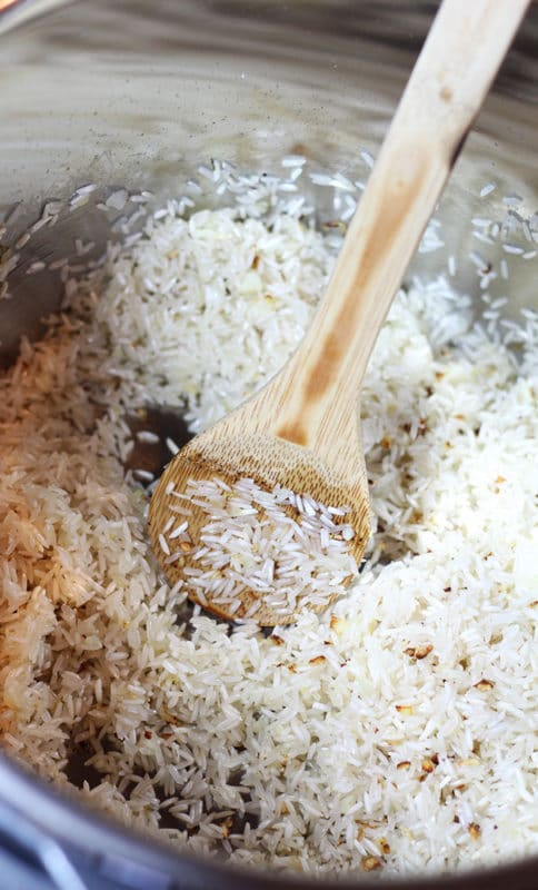 Instant Pot containing white grain rice, wooden spoon to stir.