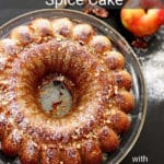 Apple Pumpkin Spice Bundt CAke on a glass container topped with glazed and fresh pecans, apples and cinnamon on table.