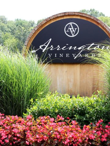 A picture of the Arrington Vineyards sign with red flowers and green hedges.